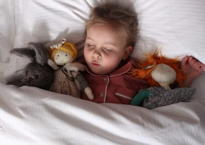 Girl asleep in a comfy bed with cuddly toys